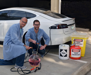 Electrosynthesis Researchers -- Figure 1. Phil Baran (left) and Evan Horn use electricity (but not actually from the Tesla car pictured) to power an allylic oxidation reaction. Source: The Scripps Research Institute.
