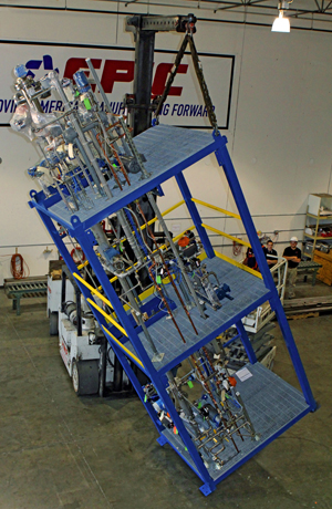 MODULAR UNIT -- Figure 2. A mobile hoist moves one of the skids at the fabrication facility.